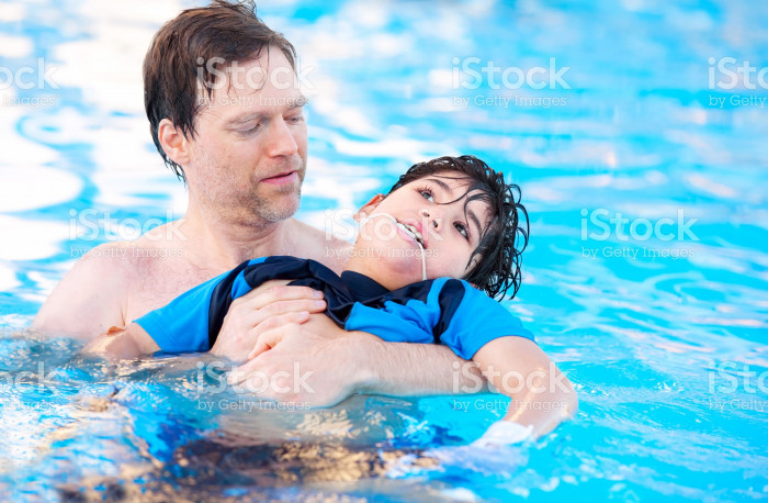 483393942-father-swimming-in-pool-with-disabled-child