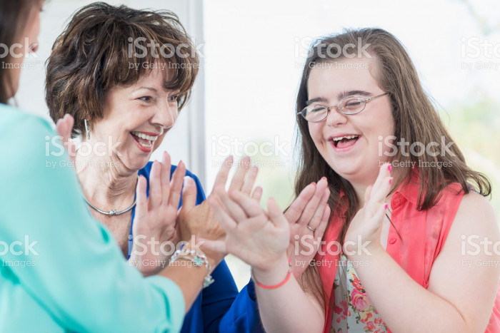 514514204-down-syndrome-girl-with-family-playing-games